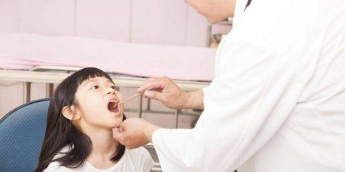 Thăm khám trẻ bị sốt viêm họng